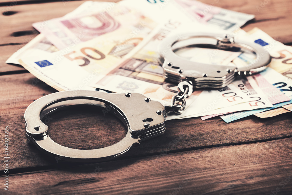 Fototapeta financial crime concept - money and handcuffs on the table