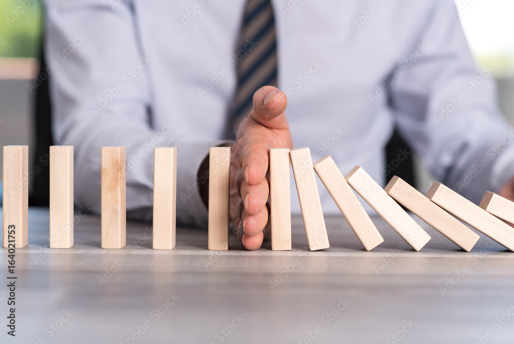 Fototapeta Concept of business control by stopping domino effect