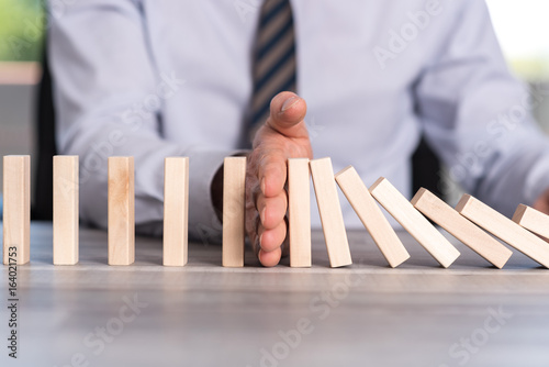 Fényképezés Concept of business control by stopping domino effect