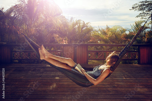 Woman in dress is resting in a hammock on the terrace against the background of sunset in jungle.