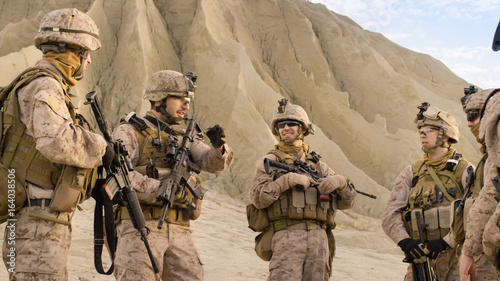 Photo Shot of Fully Equipped Group of Soldiers Standing in a Circle and Planning Their Actions Before Military Operation in the Desert