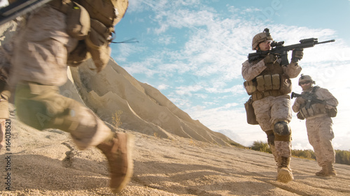 Fotografía  Squad of Fully Equipped and Armed Soldiers Running and Aiming in Single File in the Desert