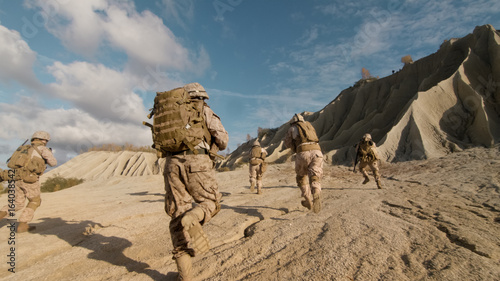 Photo Shot of Squad of Soldiers Running Forward and Atacking Enemy During Military Operation in the Desert