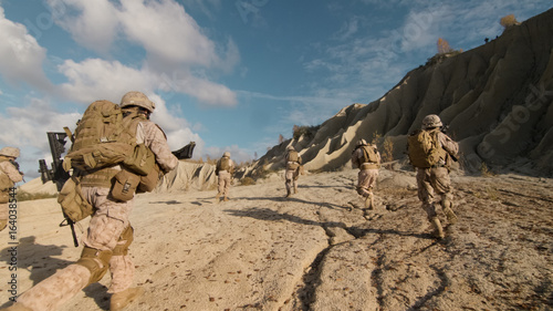 Εκτύπωση καμβά Shot of a Squad of Soldiers Running Forward and Atacking Enemy During Military Operation in the Desert
