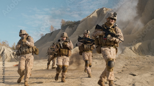 Αφίσα Squad of Fully Equipped, Armed Soldiers Running and Attacking During Military Operation in the Desert