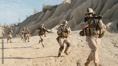 Photo  Squad of Fully Equipped, Armed Soldiers Running in the Desert
