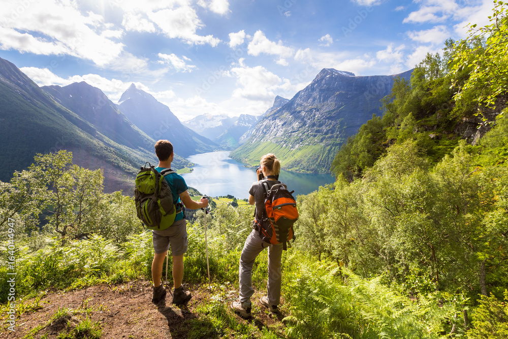 Fototapety, obrazy: Two hikers at viewpoint  in mountains with lake, sunny summer