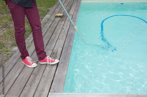 Man cleaning the blue swimming pool from leaves with ...