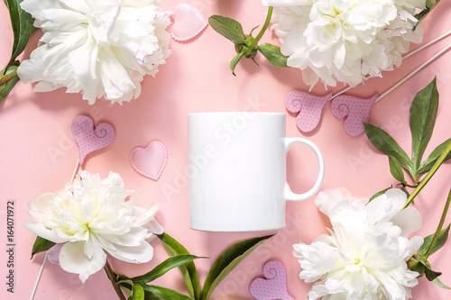 White coffee mug with white peonies and hearts on pink background.