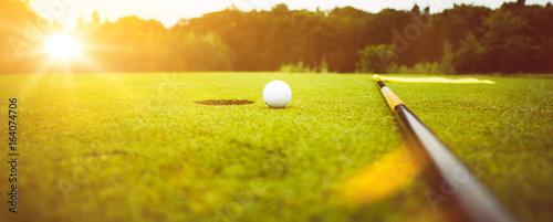 Fotomural Golfplatz im Abendrot mit Loch und Golfball und Fahne