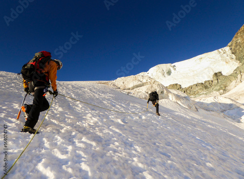 Foto op Plexiglas Alpinisme two male mountain climbers on a rope crossing and climbing a steep glacier in the Barre des Ecrins National Park in the French Alps