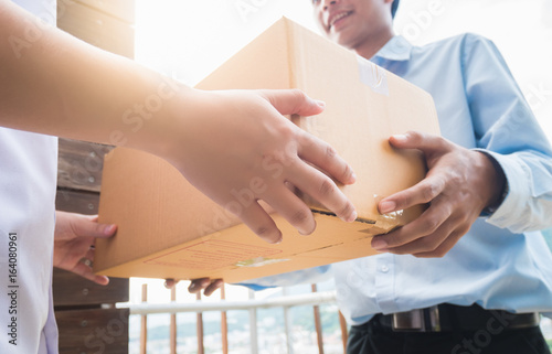 Fotografía  Hand of asia woman are receive a box from delivery man in delivery service concept