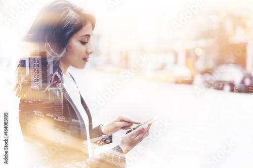Fotografie, Obraz  Double exposure successful female employer typing text message on her cellphone