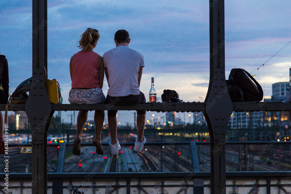 Fototapety, obrazy: Young couple in love on romantic date sitting on railway bridge with a bottle of wine and watching the sunset over Munich urban city center. Just the two of us.