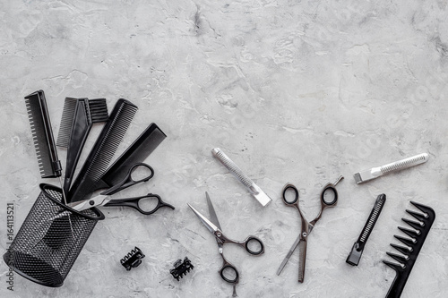 Plakat Miejsce pracy fryzjera. Grzebienia i sciccors na popielatym stołowym tło odgórnego widoku copyspace