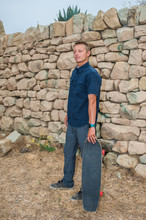 California Skater Guy Standing With His Skateboard Near Stone Wall.