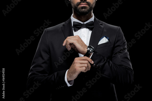 Valokuva cropped view of businessman in bow tie and tuxedo with watch, isolated on black