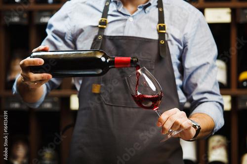 Cuadros en Lienzo Male sommelier pouring red wine into long-stemmed wineglasses.