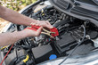 Hands of car mechanic using car battery jumper cable