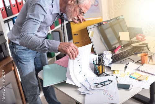 Fotografía  Disorganized businessman looking for documents, light effect