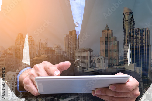 Photographie  Double exposure of businessman using tablet with long exposure city night