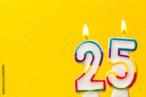 Tela  Number 25 birthday celebration candle against a bright yellow background