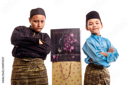 Fotografía  Young Muslim  boys  in malay traditional  clothes with shopping bags for Eid Al Fitr, isolated on white