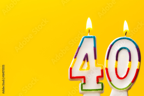 Tela  Number 40 birthday celebration candle against a bright yellow background