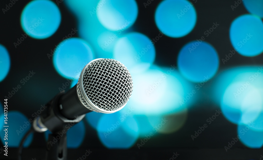 Fototapeta Microphone on abstract blurred of speech in seminar room or speaking conference hall light, Event concert bokeh background