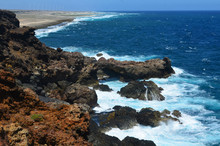 Aruba's Coastline With Lava Rock And Waves Crashing