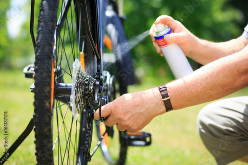 Fotografía Senior man hands spraying an oil to chain from the wheel bike, doing maintenance