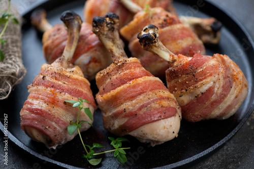 Fotografía  Close-up of oven-baked chicken legs wrapped in bacon, selective focus, horizonta