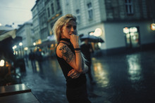 Young Woman With Tattoo On Shoulder Stands On City Street In Evening In Rain.