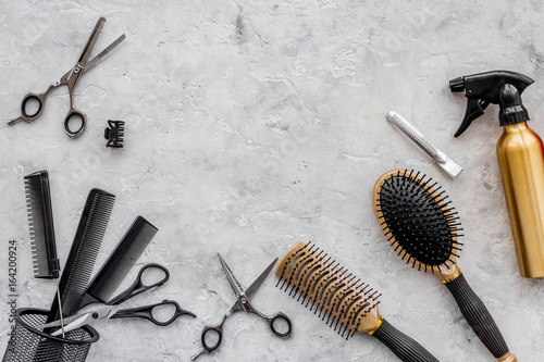 Hairdresser workplace. Combs and sciccors on grey table background top view copyspace