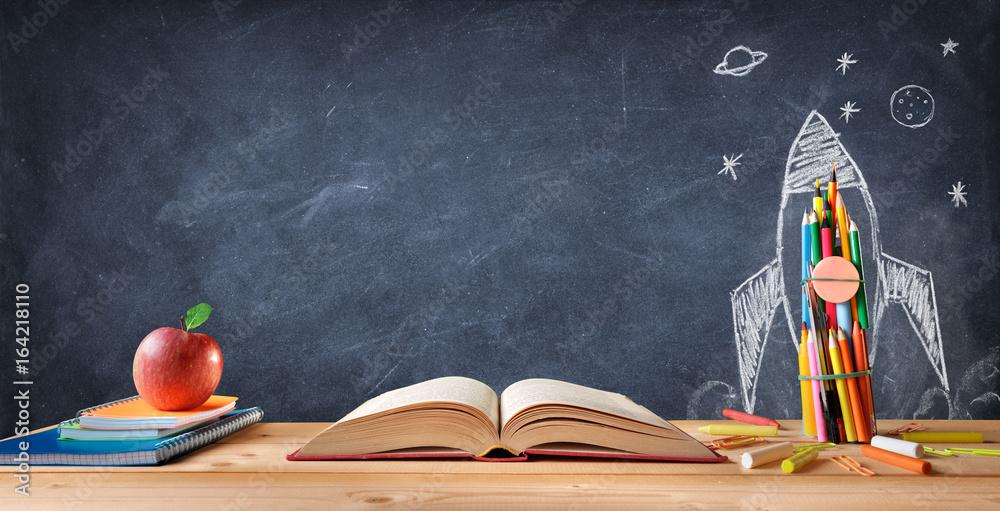 Fototapeta Start School Concept - Supplies On Desk And Rocket Drawn On Blackboard