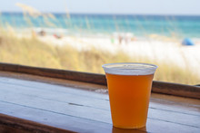 A Cold Beer Sits On The Bar With A View Of The Beach