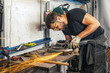A young man welder in a black T-shirt, glasses and construction gloves grinder metal an angle grinder in the garage, in the background a lot of tools, sparks fly to the side