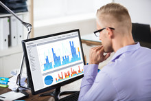 Businessman Looking At Graph On Computer