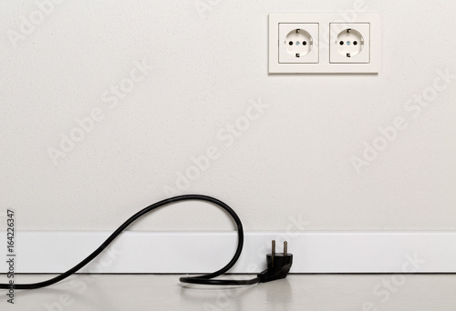 Fotografía  Black power cord cable unplugged with european wall outlet on white plaster wall
