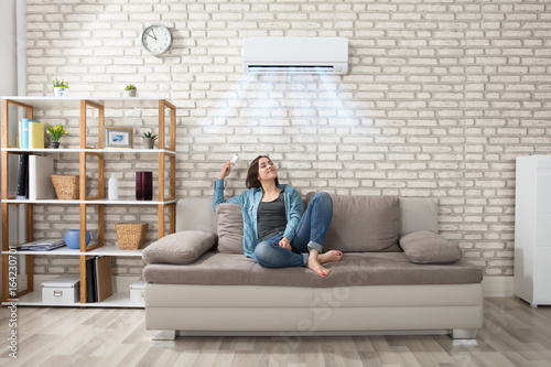 Fotomural  Woman Relaxing Under The Air Conditioner
