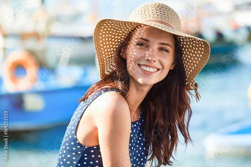 Fototapeta premium Portret pięknej kobiety w słomkowym kapeluszu. Śmiejąca się dziewczyna. Czas letni