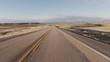 Driving USA: Spectacular point of view car shot speeding across desert grasslands at sunrise or sunset, Wyoming