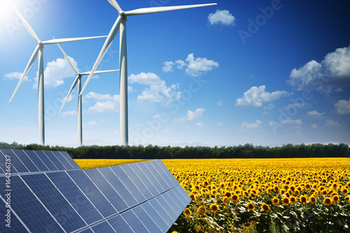 Green energy concept with solar panels and wind turbines on a sunflower field