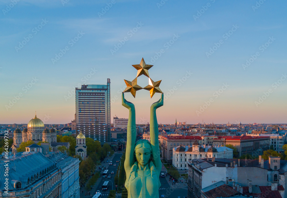 Fototapety, obrazy: Beautiful sunset view in Riga by the statue of liberty - Milda. Freedom in Latvia. Statue of liberty holding three stars over the city. Latvian spirit.
