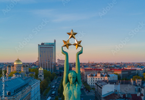 Obraz Beautiful sunset view in Riga by the statue of liberty - Milda. Freedom in Latvia. Statue of liberty holding three stars over the city. Latvian spirit. - fototapety do salonu