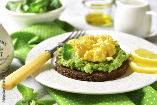 Rye toast with scrambled egg and avocado - concept of healthy breakfast.