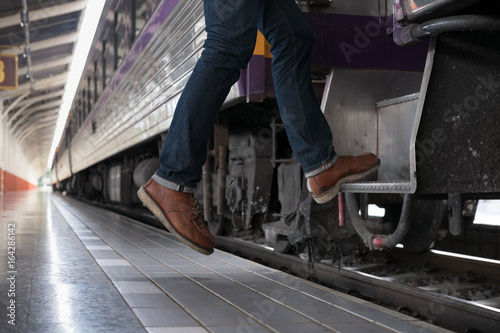 Fotografie, Obraz  young man, tourist or traveler stepping up to the train on railway at train station