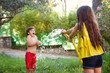 boy and girl playing with water hose