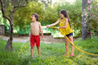 girl spraying brother with water hose