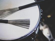 Close Up Drum With Jazz Brush Drumsticks On Black Background